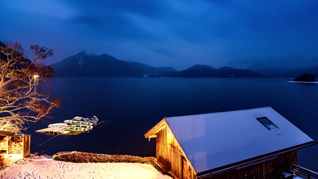 vídeos de stock e filmes b-roll de boathouse and rowboats on lakeshore with mountain range in background time-lapse - alemanha