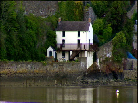 boathouse seen across harbour laugharne wales - seicht stock-videos und b-roll-filmmaterial