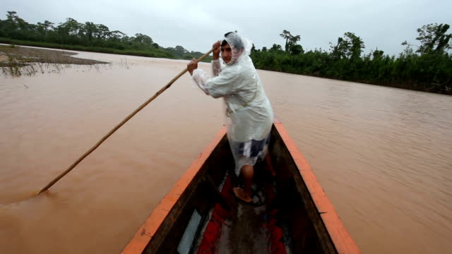 Boating along Quiquibey river, man with a rod pushes the boat away from the banks, Bolivia, Amazon