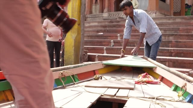 boatman banks a boat at the ghats /the term ghat refers to a series of steps leading down to a body of water, particularly a holy river. this is such... - holy water stock videos & royalty-free footage