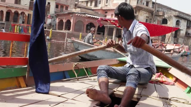 a boatman rows a boat to the ghats /the term ghat refers to a series of steps leading down to a body of water particularly a holy river this is such... - place of worship stock videos & royalty-free footage