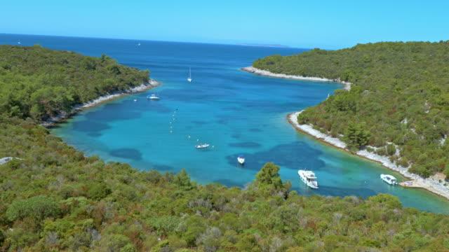 vídeos de stock, filmes e b-roll de aerial barcos ancorados na baía belo mar - cres croácia