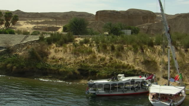 vidéos et rushes de ws, ha, pan, boats and deck at nile river, hills in background, egypt - 2009
