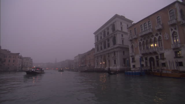 vídeos de stock, filmes e b-roll de boats and gondolas pass by multi-story buildings along both sides of a foggy venice canal. - meteorologia
