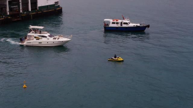 boats and jetski in hong kong harbor - spoonfilm stock-videos und b-roll-filmmaterial