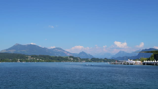 boats and pedal boats on lake lucerne with mount rigi in background. - lake lucerne stock videos & royalty-free footage