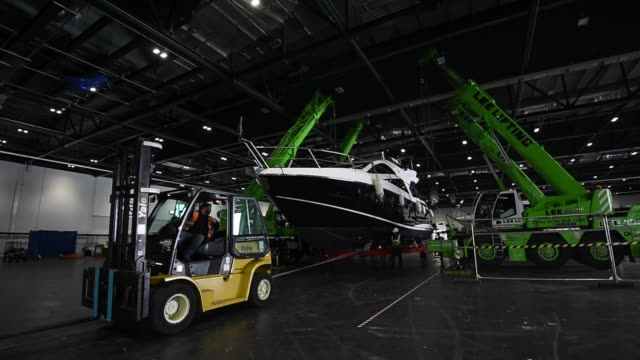 boats are lifted off their transport trailers into excel london so they can be displayed at the london boat show at excel on december 18 2015 in... - london boat show stock videos and b-roll footage