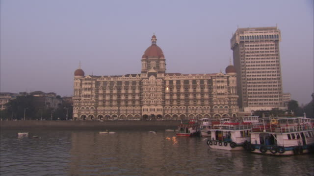 Boats are moored in the harbour near the Taj Mahal Hotel Mumbai.Available in HD.
