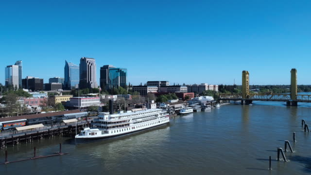 boats at the pier in old sacramento waterfront district, with the remote view of tower bridge in the backdrop. aerial drone video with the backward camera motion. - sacramento stock videos & royalty-free footage