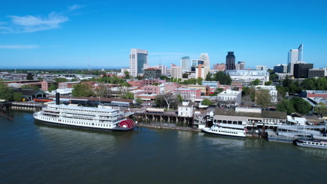 boats at the pier in old sacramento waterfront district, with the remote view of sacramento downtown in the backdrop. aerial drone video with the panoramic camera motion. - sacramento stock videos & royalty-free footage