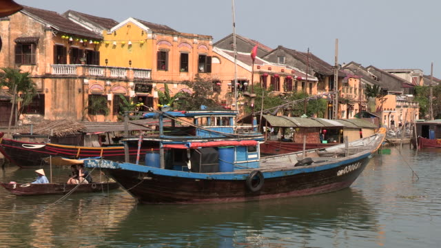 boats bob at anchor in the harbor of the ancient city of hoi an vietnam - sampan stock videos & royalty-free footage