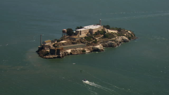 Boats create wakes as they cruise around Alcatraz Island.