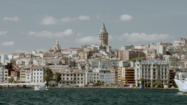 pov boats cruising through the bosphorus strait past the coastline crowded with buildings / istanbul, turkey - vagare senza meta video stock e b–roll