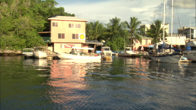 boats dock at waterfront homes in a paluan community on the philippine sea. - micronesia stock videos & royalty-free footage