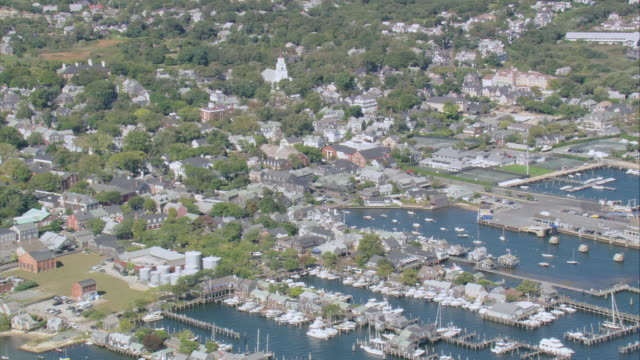 AERIAL Boats docked at extensive piers with more anchored in the inlets and the town beyond / Nantucket, Massachusetts, United States