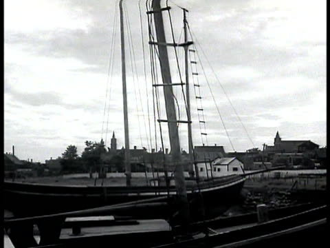 vídeos de stock, filmes e b-roll de boats docked in nova scotia town bg modest harbor houses on waterfront w/ row boat farmer tilling soil in garden w/ hoe cu hoe moving between new... - 1943