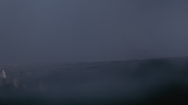 a boats emerges out of a fog and floats away through the night. - emergence stock videos & royalty-free footage