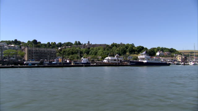 Boats float alongside a dock in the River Dart below Dartmouth Naval College. Available in HD.