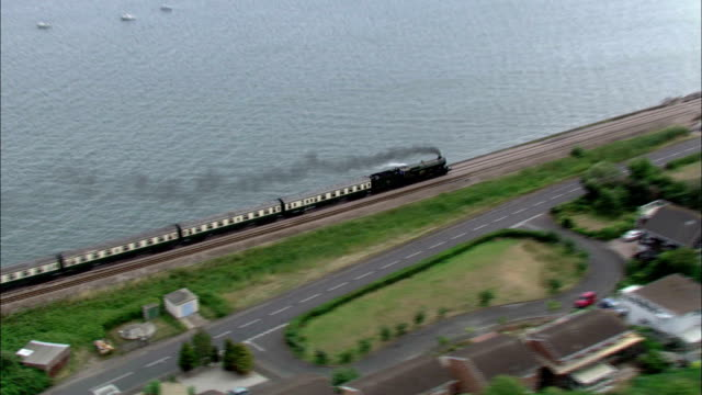 Boats float in a harbor as a steam train passes on the south west coast. Available in HD.