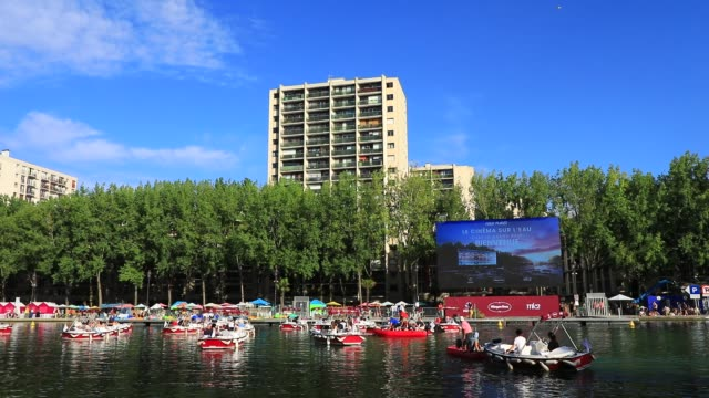"""boats float in front of the giant screen during paris plages launch of """"le cinema sur l'eau"""" with the screening of """"le grand bain"""" at bassin de la... - laziness stock videos & royalty-free footage"""