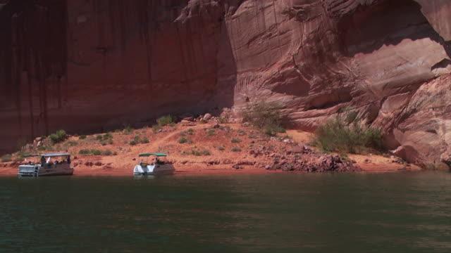 stockvideo's en b-roll-footage met boats float near the shore of lake powell. - powellmeer