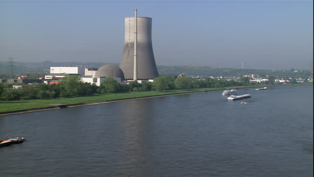 boats float through a river, passing by a nuclear power plant. - akw reaktorbereich stock-videos und b-roll-filmmaterial