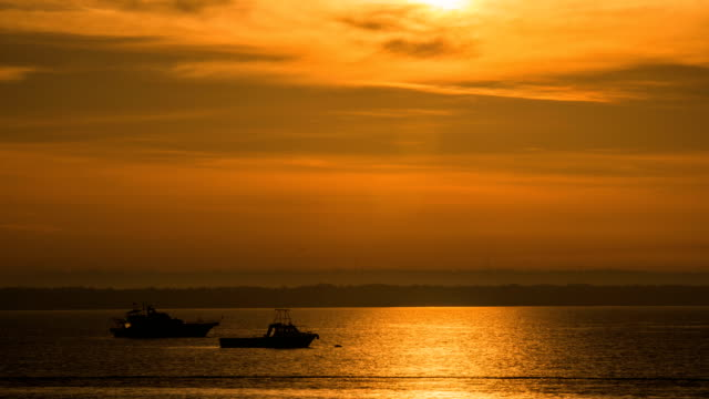boats floating on the ocean at sunrise / darwin, australia - seascape stock videos & royalty-free footage