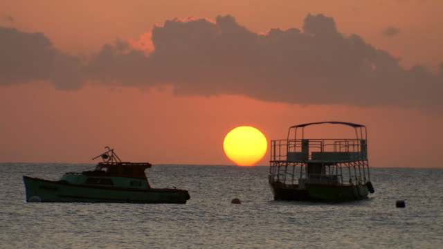 WS Boats floating on the sea at sunset  / Brightown, Barbados