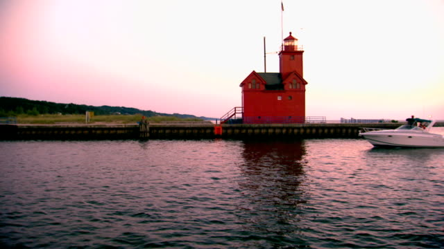 boats going in and of a channel at sunset past a light house - vagare senza meta video stock e b–roll