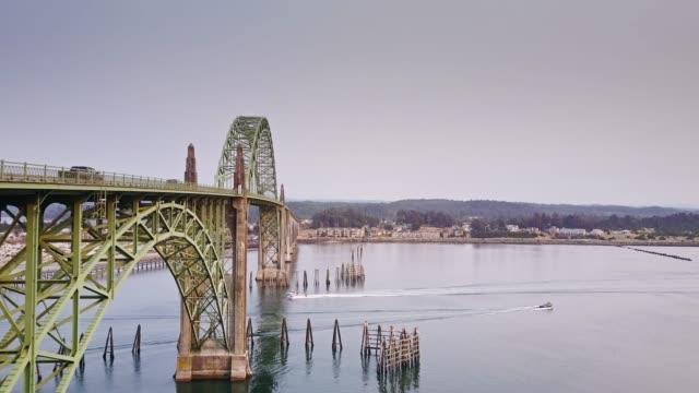 boats going under yaquina bay bridge, oregon - aerial view - newport oregon stock videos & royalty-free footage