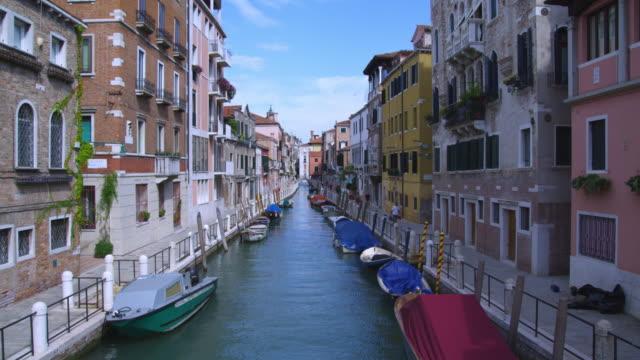 vidéos et rushes de boats in a canal float alongside the waterfront sidewalks in venice. - canal eau vive