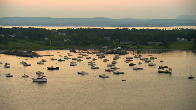 low aerial, boats in harbor at dusk, owls head, maine, usa - oceano atlantico del nord video stock e b–roll