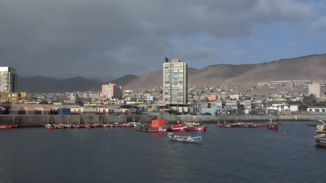 ws pan boats in harbor with cityscape and mountains in background, antofagasta, chile - antofagasta region stock videos and b-roll footage