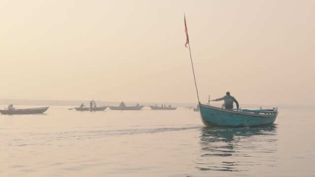 Boats in the haze on the Ganges river at sunrise - Slow Motion