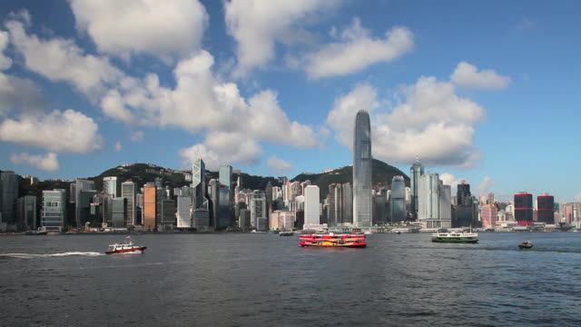boats in view across hong kong harbour looking towards hong kong island from tsim sha tsui, kowloon. - bank of china tower hong kong stock videos and b-roll footage