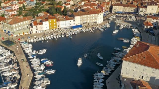 vídeos de stock, filmes e b-roll de aerial barcos deixando porto de cidade pequena em dia ensolarado - cres croácia