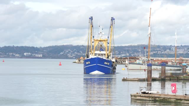 stockvideo's en b-roll-footage met boats moored and moving in and out of brixham harbour in devon, england. - brexit