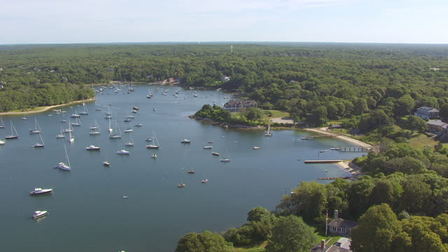 ws aerial pov boats moored at quissett harbour with tree area / falmouth, massachusetts, united states - massachusetts stock videos & royalty-free footage