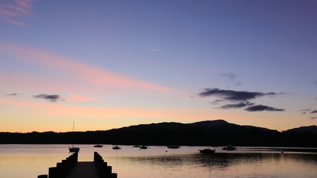 boats moored at waterhead at the head of lake windermere, ambleside at dusk, lake district, uk. - jetty stock videos & royalty-free footage