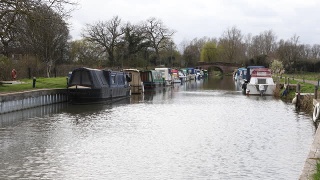 boats moored by the side of a canal in the english countryside - barge stock videos & royalty-free footage