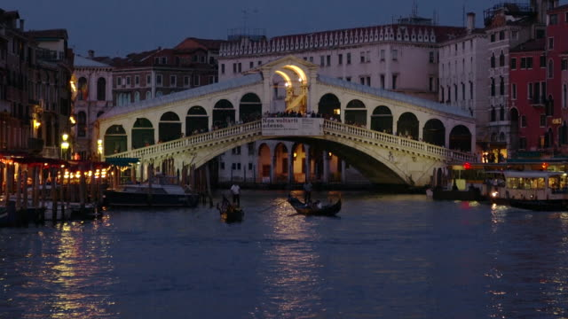 boats move along the grand canal near the ponte di rialto in venice, italy. - ponte stock videos & royalty-free footage