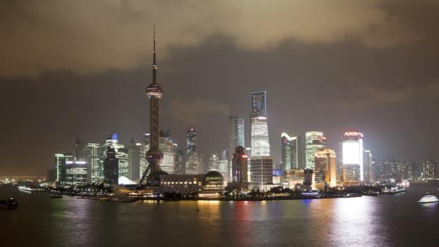 Boats move along the Huangpu River near the illuminated Shanghai, China skyline.