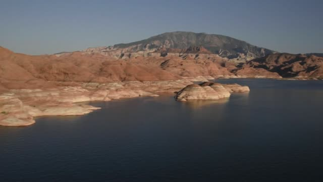 boats move past the shore on lake powell in this aerial photograph taken above page arizona us on thursday june 25 2015 shots camera pans over rock... - lake powell stock videos and b-roll footage