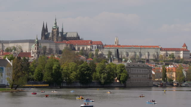 ws boats moving in vltava river, st. vitus cathedral in backgrounds / prague, czech republic - river vltava stock videos and b-roll footage