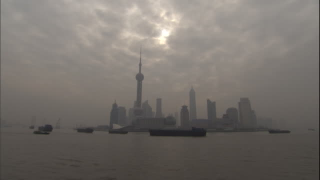 ws boats moving past cityscape on yangtze river on overcast day/ shanghai, china - bedeckter himmel stock-videos und b-roll-filmmaterial