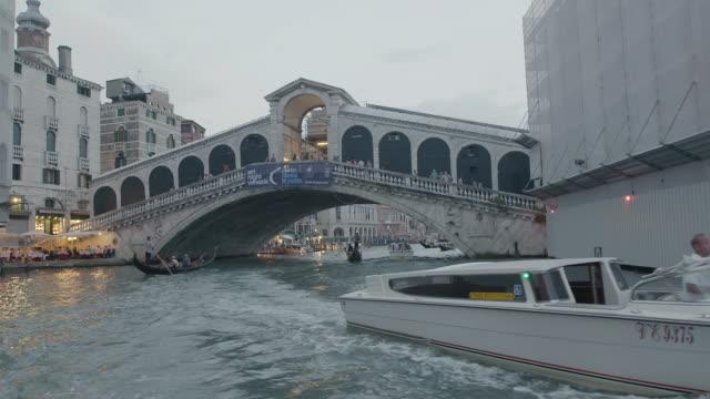 WS POV Boats moving under Rialto Bridge at dusk / Venice, Italy