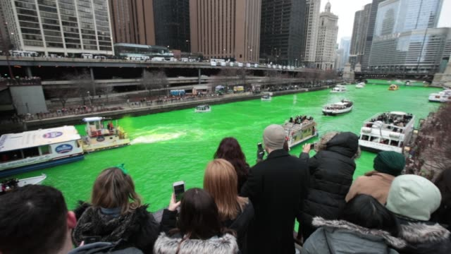 boats navigate the chicago river shortly after it was dyed green in celebration of st. patrick's day on march 17, 2018 in chicago, illinois. dyeing... - st. patrick's day stock videos & royalty-free footage