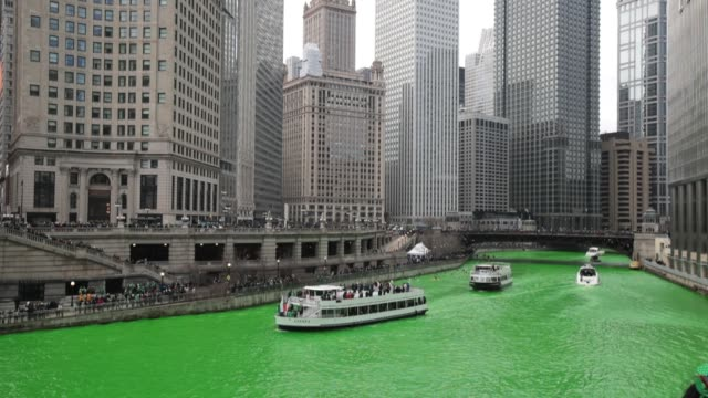 boats navigate the chicago river shortly after it was dyed green in celebration of st. patrick's day on march 17, 2018 in chicago, illinois. dyeing... - chicago river stock videos & royalty-free footage