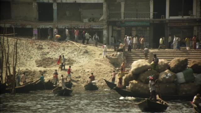 ws, boats on buriganga river, people walking on dilapidated riverbank, dhaka, bangladesh - dhaka stock videos and b-roll footage