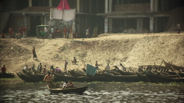 ms, boats on buriganga river, people walking on dilapidated riverbank, dhaka, bangladesh - dhaka stock-videos und b-roll-filmmaterial